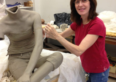 Clay figure being constructed - adding an arm